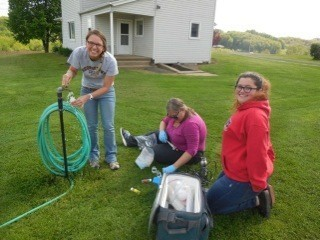 Group of students sitting on ground with a hose