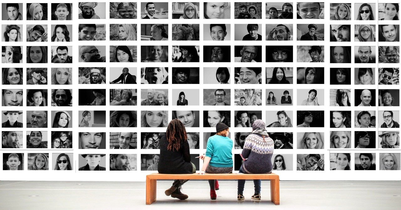 People sitting on bench looking at black and white images of people in a gallery